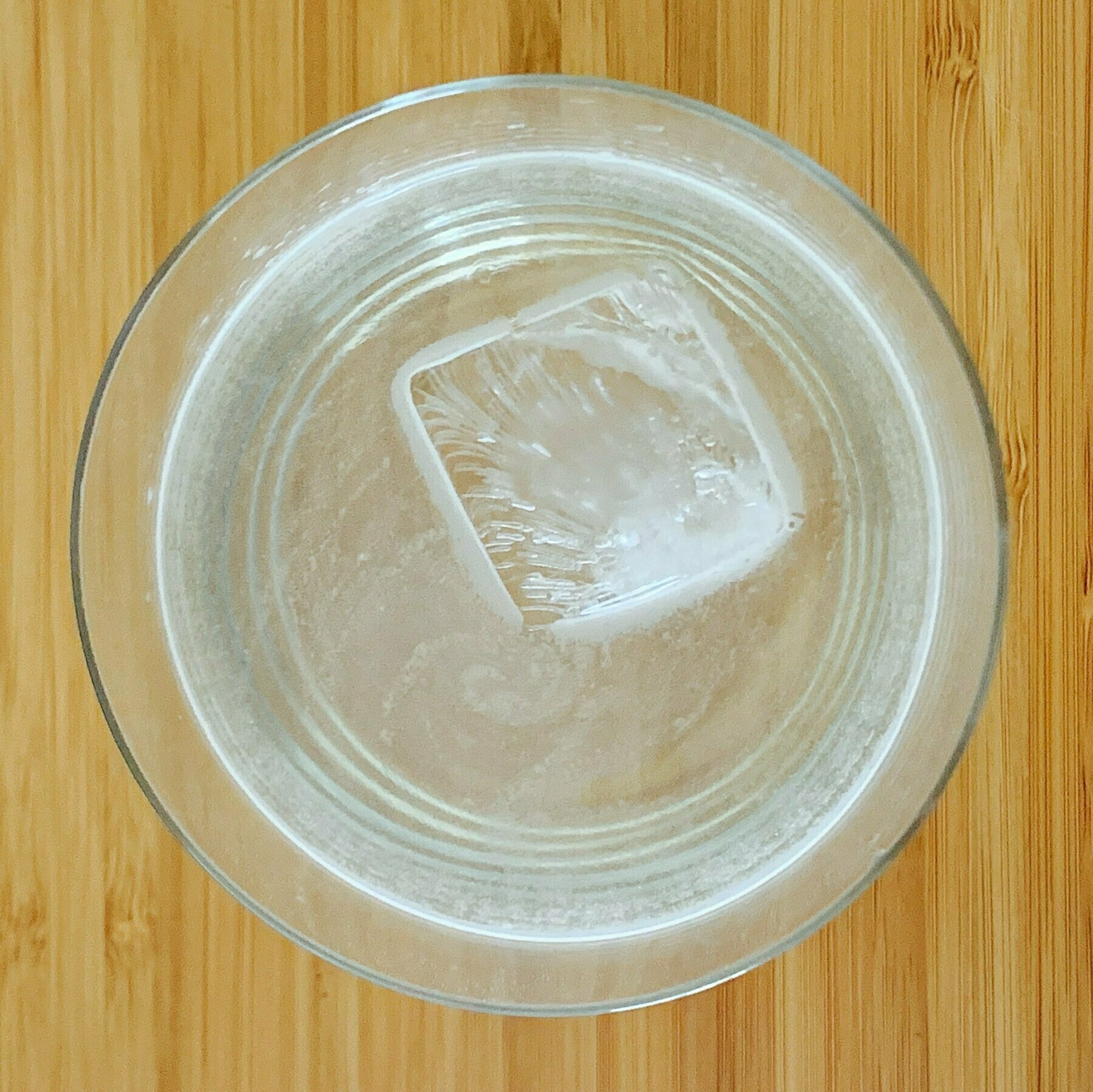 Top down look at a glass of water with an ice cube
