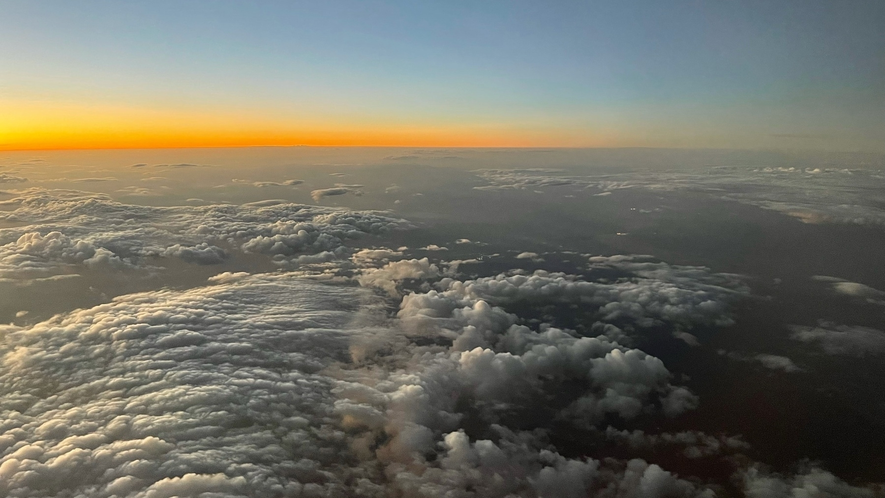 view out an aiplane window at sunset with clouds and an orange ribbon at the horizon