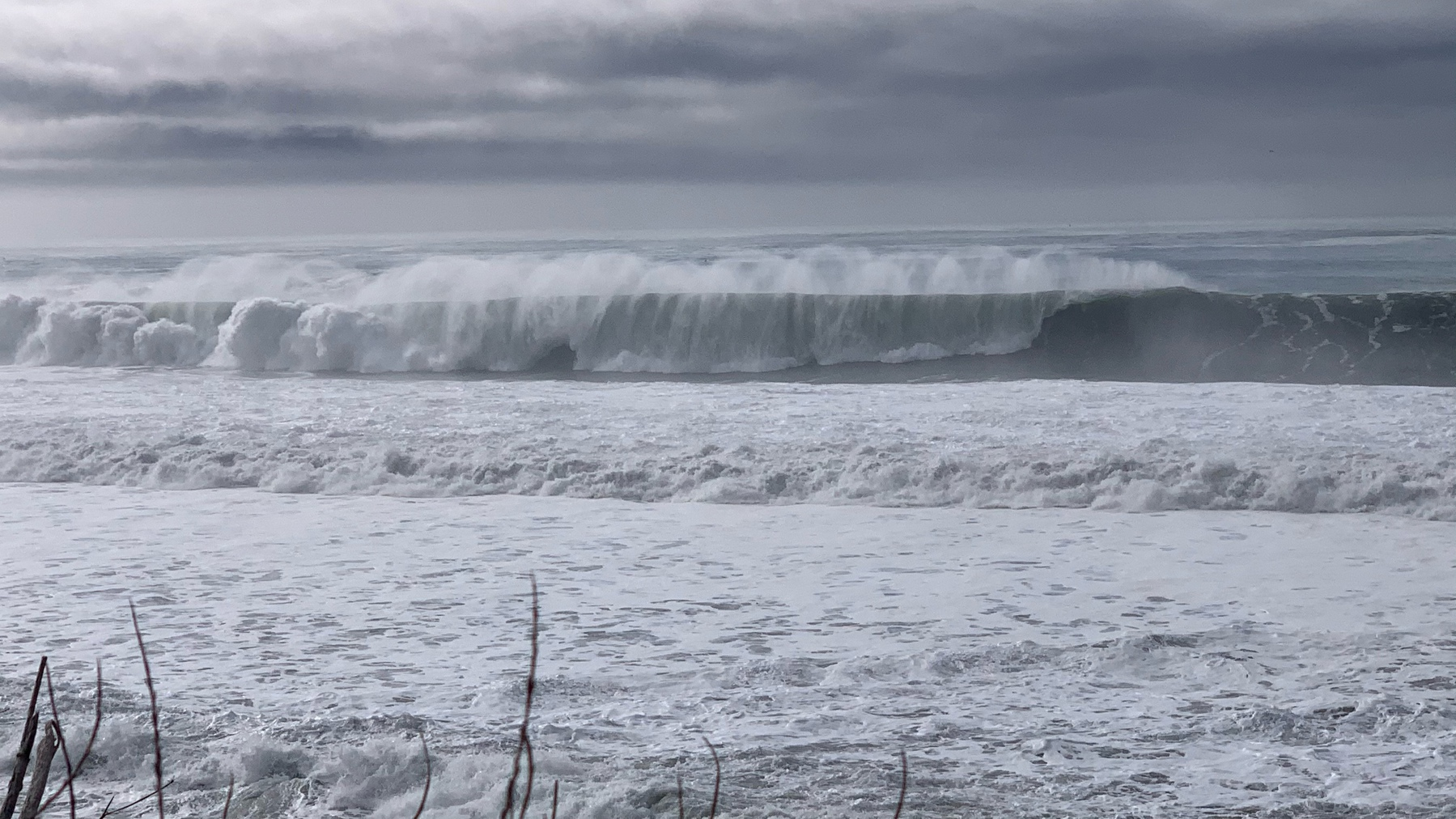 waves crashing, with a ghost wave in front of a cresting wave